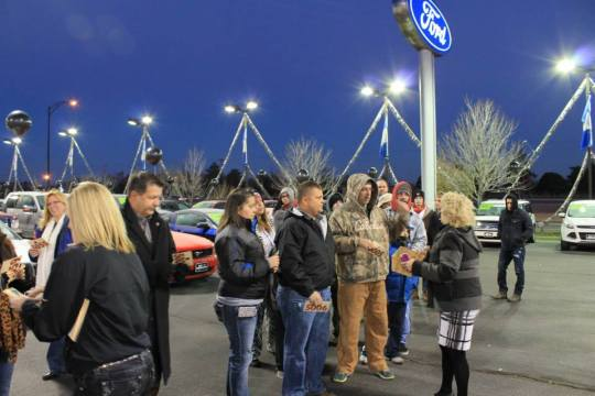 People in line receive their numbers for Black Friday Cars.